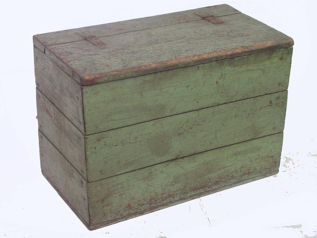Vedkasse av furu, opprinnelig malt 1700-talls rødbrun. Senere malt lys grønn, bortsett  Innvendig umalt. I hjørnene vertikale stolper, hvori sidene er spikret med  bord på sidene, to i bunnen.  Rettsidet stort skrin med rektang. grunnflate.   Lokket er festet med to jernbeslag og er uten lås, og opptar ca. 3/4  Tilstand: noe slitt og oppripet i overflaten, ellers god.  Datering: nåværende låsbeslag og den lyse grønnmaling 1800-årene.