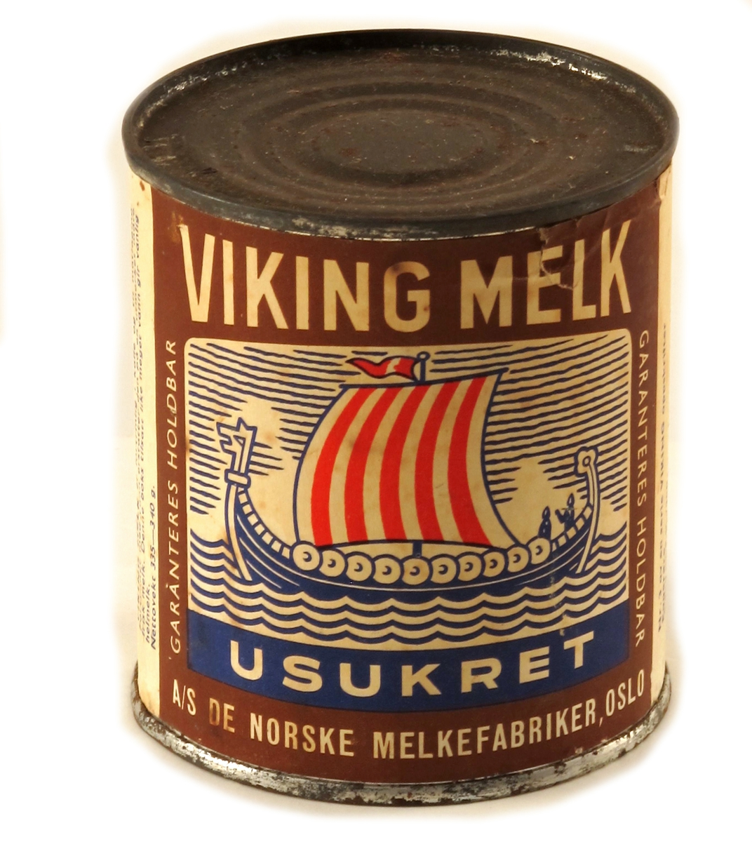 Sylinderformet  boks av valset jernblikk, falset kant, trykt etikett, hermetisert melk. Etikett av papir.