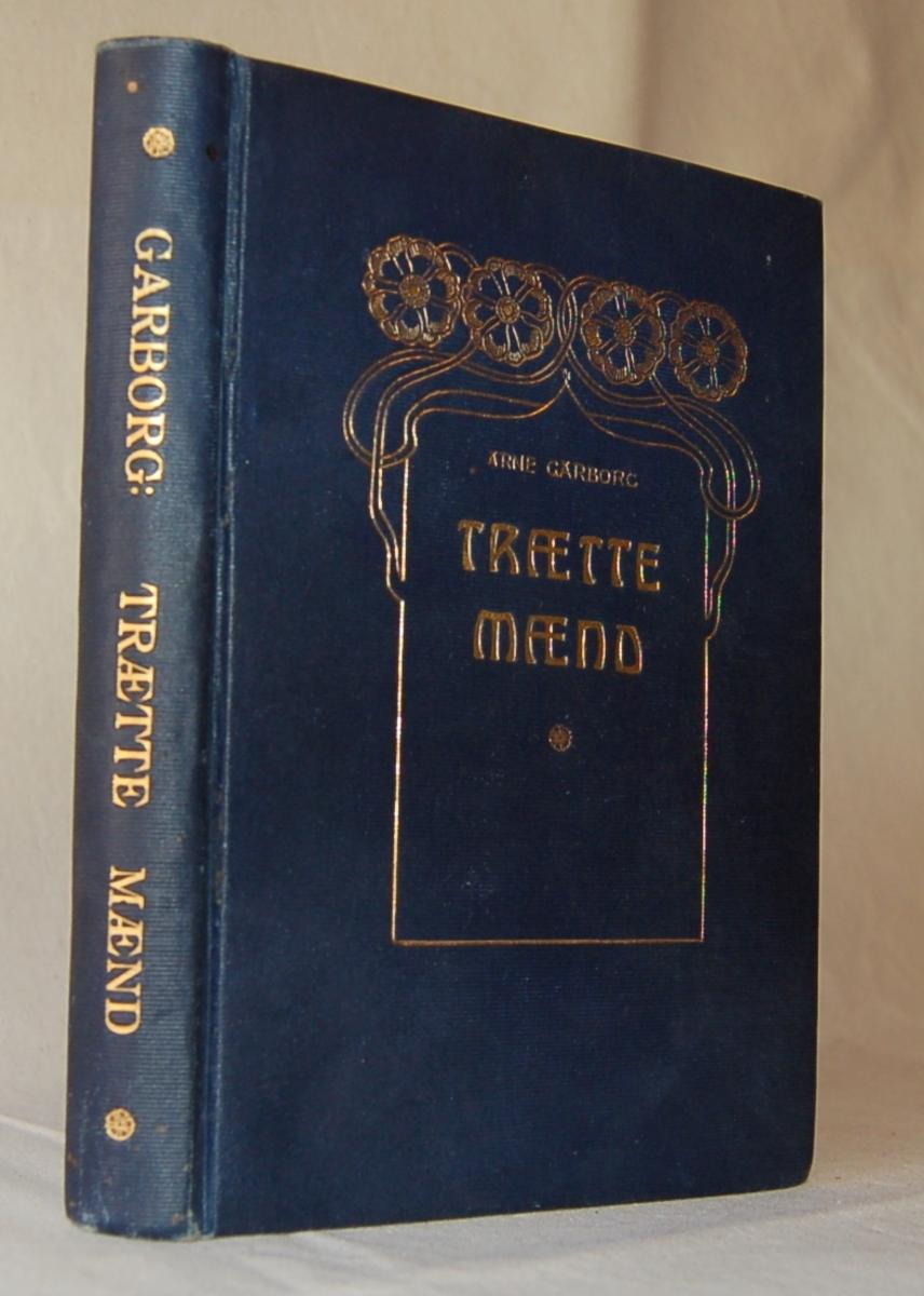 På bokens forside: Stiliserte bokstaver i gull på blå bakgrunn