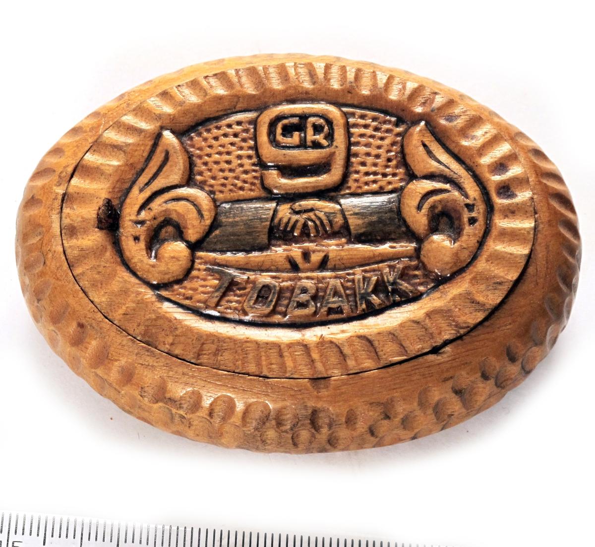 Håndslag, m.m. Akantusblad. Bokstavene GR i et 9-tall. På lokkets underside bilde av en brakkeleir.