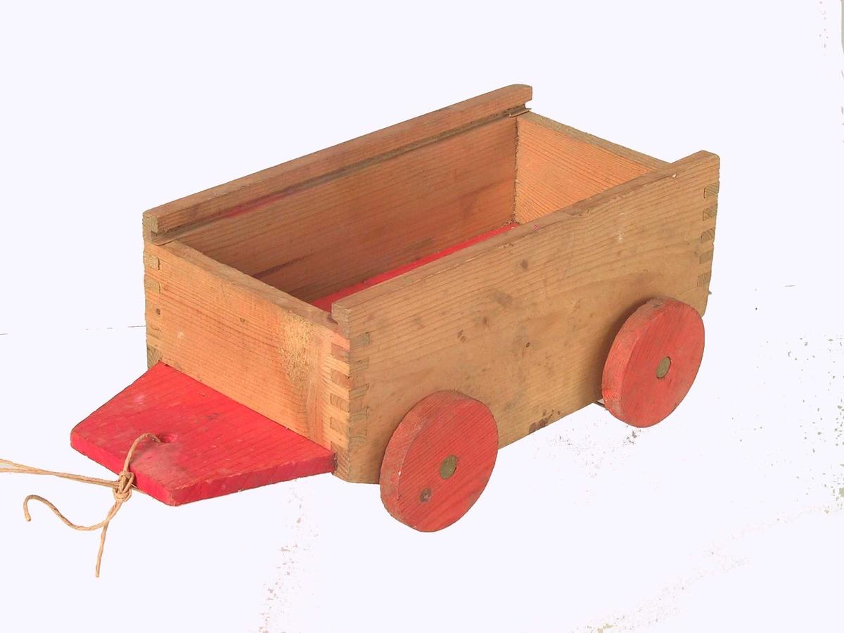 Form: Liten vogn/henger med 4 hjul, har trolig hatt skyvelokk. Bunnen stikker frem foran sideveggene foran, har et hull som det er festet en hyssing gjennom.
