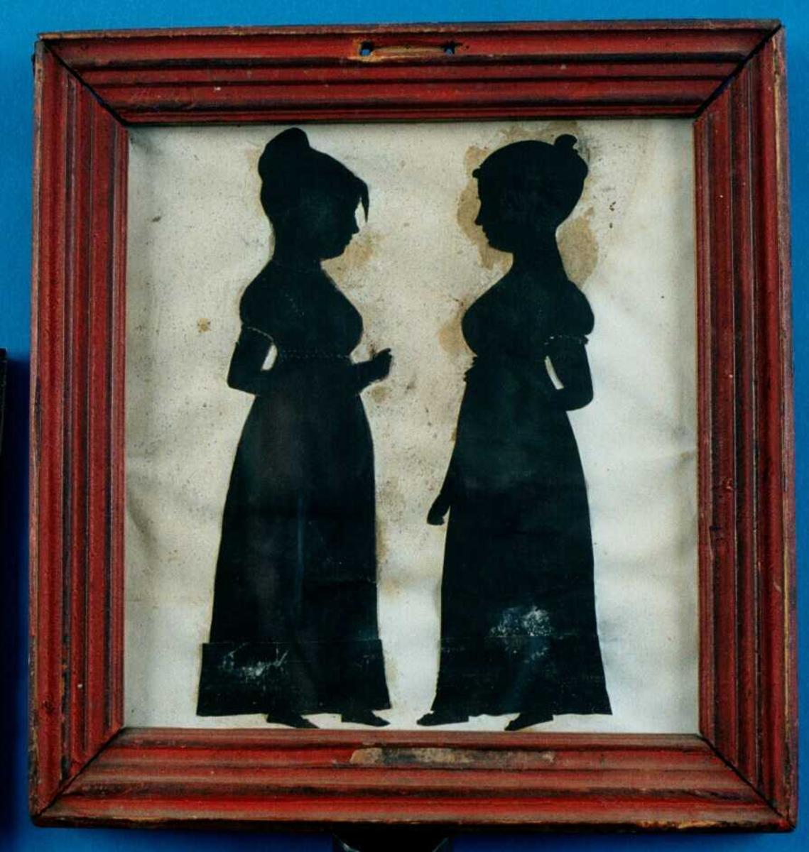 2 unge piker i helfigur med ansiktene vendt mot hverandre begge med oppsatt hår. Kledd i empirekjoler.  Silhouetter av frkn. Norberg og Hornbech. 1805.  Jentene må være født ca. 1790. 15 år i 1805.