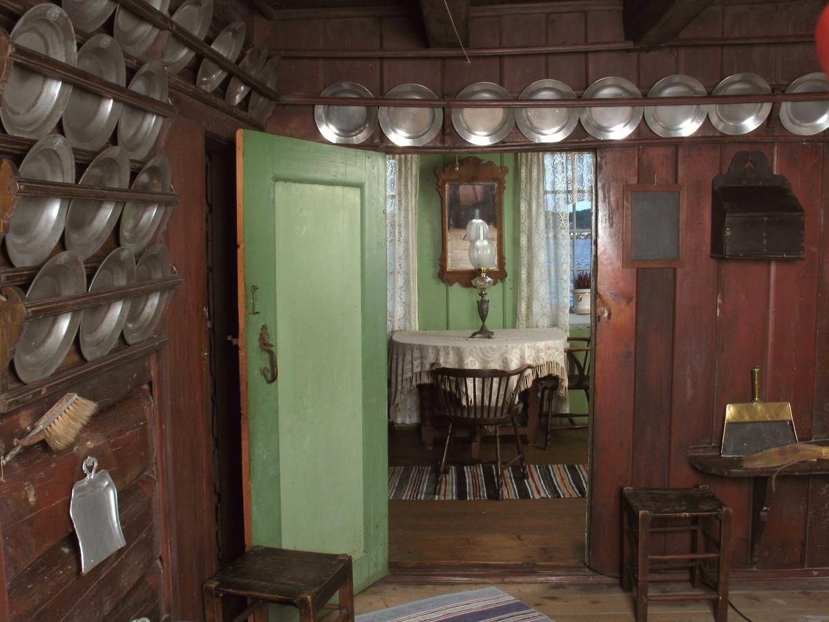Merdøgaard. Interiør kjøkkenet med utsikt gjennom dør til dagligstua, og ut på Merdøfjorden gjennom vinduet. Tinntallerkner m.m. i rekker på brunmalt vegg, grønnmalt dør.