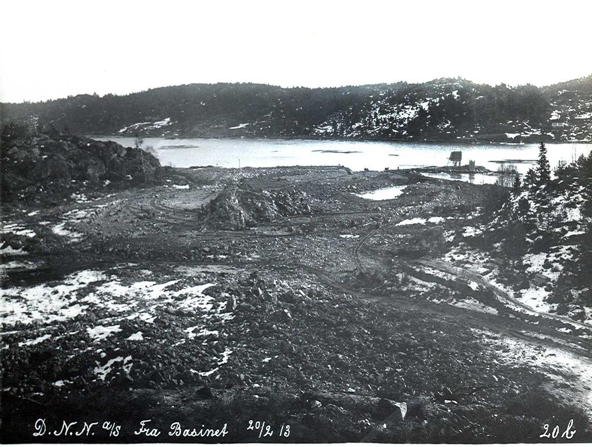 """""""20/02-1913"""" Nitriden. Utsprengning og planering av fabrikktomten. Kaianlegg skal bygges midt på bildet. I forgrunnen kommer ovnshusene. Fyrlykt nr. 612 i Norsk Fyrliste står på skjæret ved Tromøysund. Bygd 1894, flyttet til Friisøy i 1929. Tromøy i bakgrunnen."""