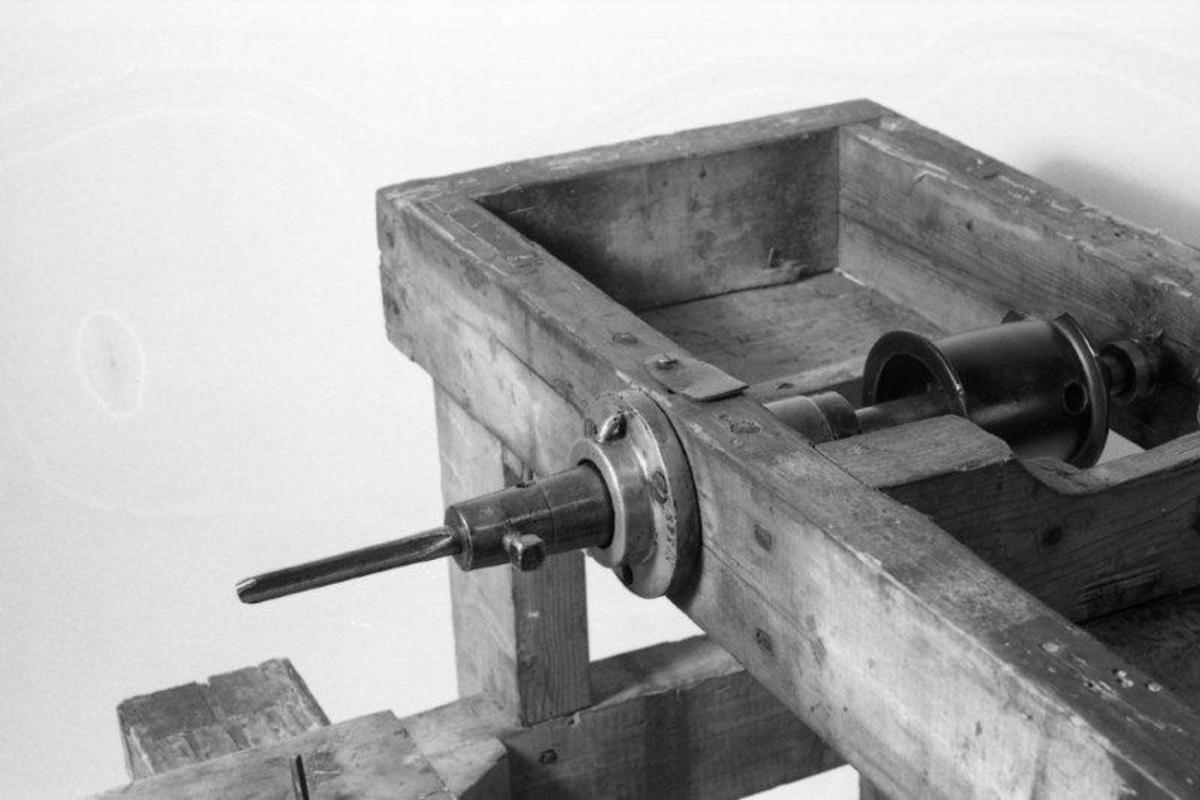 Stativets deler er tappet og spikret sammen, beina tappet opp i rammen. Rammens sidekanter gjennomsinket. Reimskiven er støpt, aksel og lager dreid.  Deler av jern og messing er trolig fabrikkfeamstilt. Maskinen hadde flere bruksområder: 1. Å lage hull i nav (der eiketappene skal sitte; disse ble deretter stemmet ut). 2: Å lage rektangulære åpninger i høyvognhekk. 3: Å lage hull i ringved og 4: Bogtrær