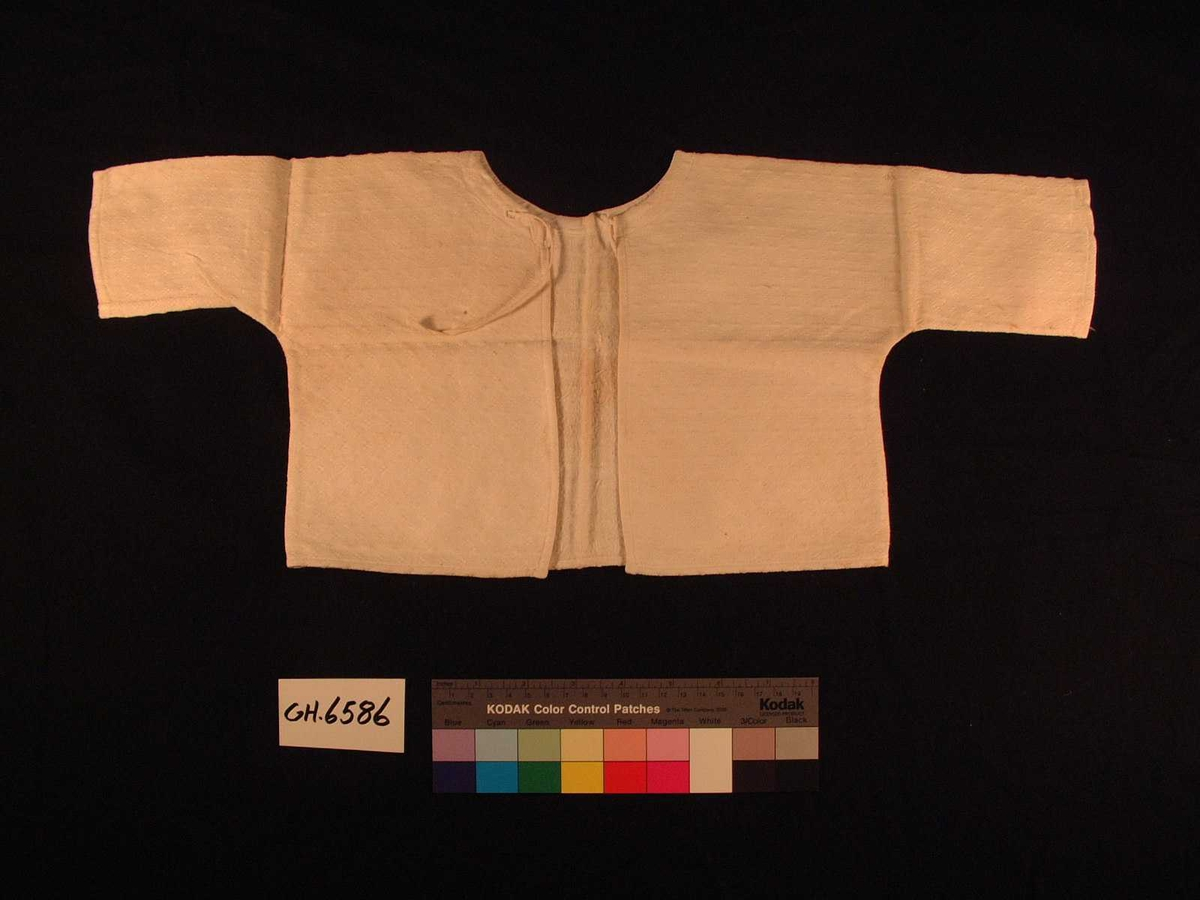 Skjorte til barn/spebarn i mønstervevd stoff.. Enkelt primærsnitt, lange ermer og åpning med knytebånd bak.