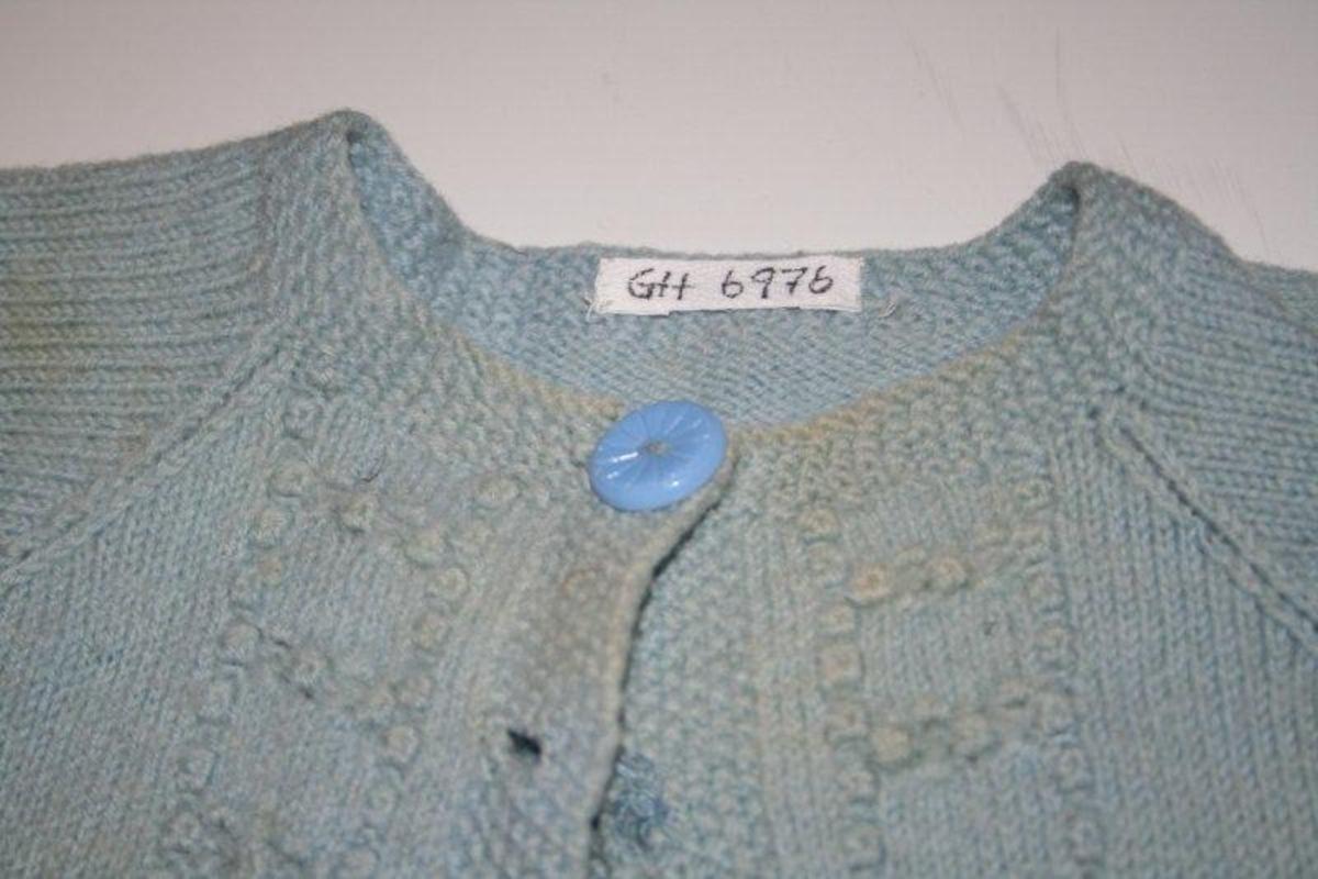 Langermet strikke med raglandfelling. Hjemmestrikket. Litt utskrånende form. En knapp lukker jakken, men der har vært fem. En stor del av jakka er med knutestrikk.