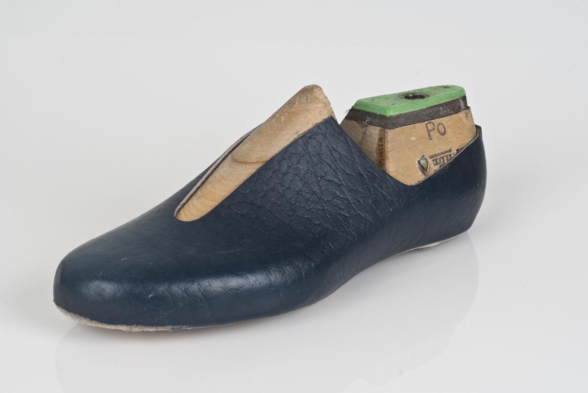 En trelest med overlæret til støvel (fabrikkstøvel). Venstrefot i skostørrelse 44, med 7,5 cm i vidde. Skinntrekket er i blåfarge. Lestekam av plast i grønnfarge, og skinn.