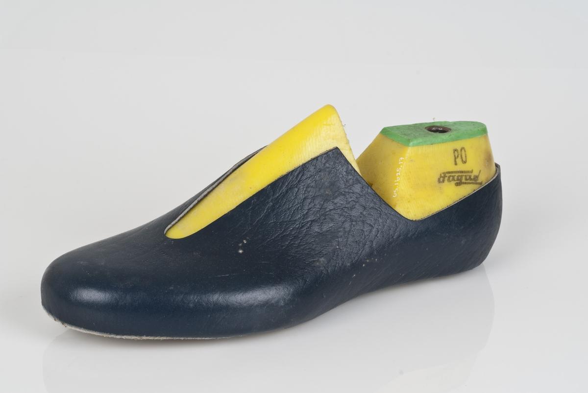 En plastlest med overlæret til støvel (fabrikkstøvel). Plastlesten er i fargen gul. Venstrefot i skostørrelse 44, med 7,5 cm i vidde. Skinntrekket er i blåfarge. Lestekam av plast i grønnfarge.