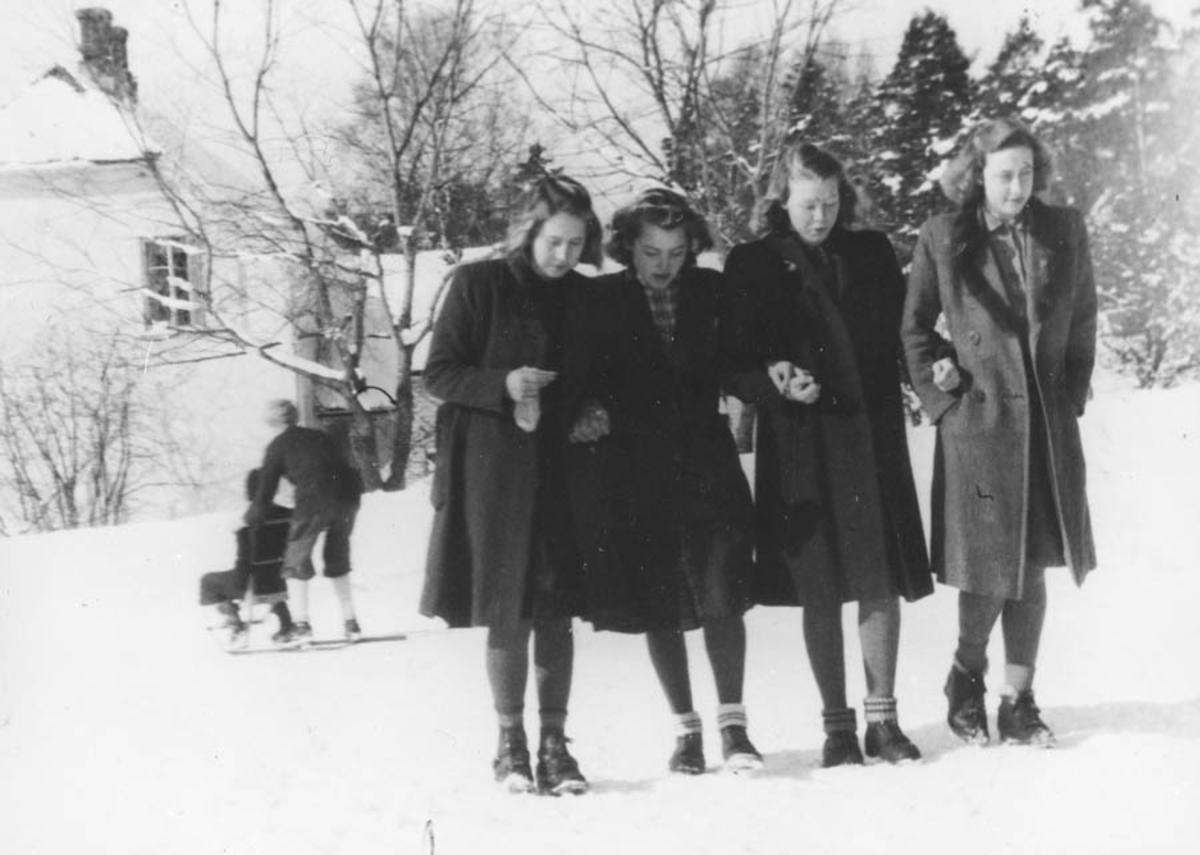 Fire jenter ute i snøen.