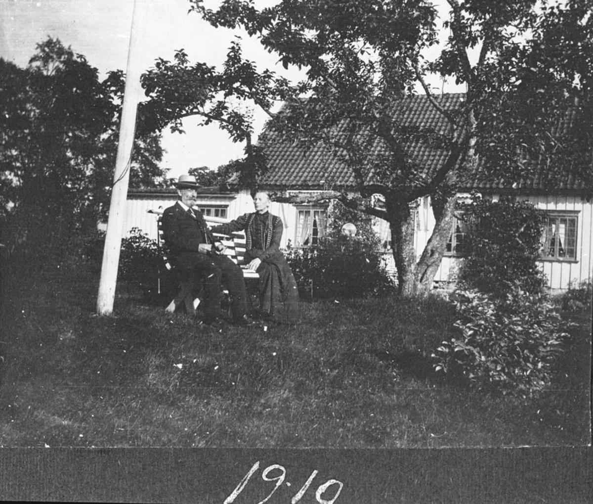 Eldre ektepar sittende på en benk i hagen.
