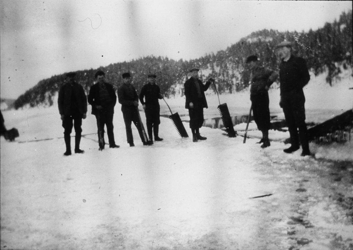 Gruppe menn med to issager ute på isen.