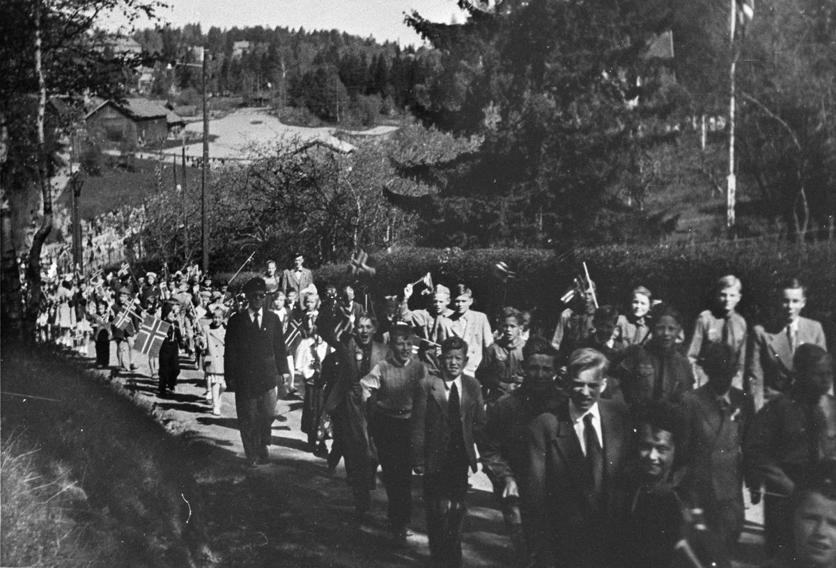 17.mai-toget går opp bakken mot kirken.