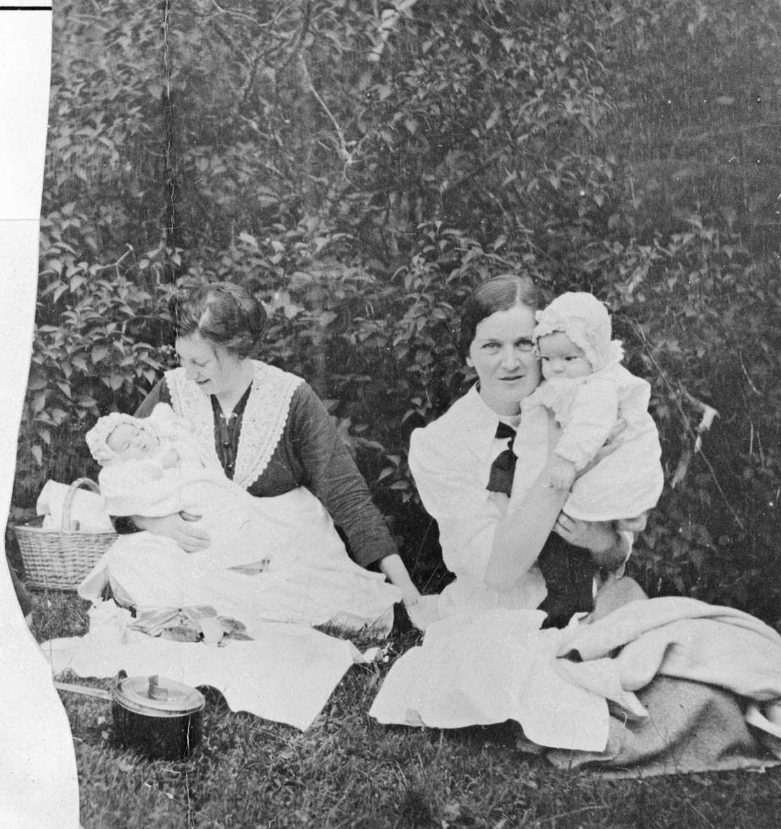 To kvinner med to spebarn ute i hage.