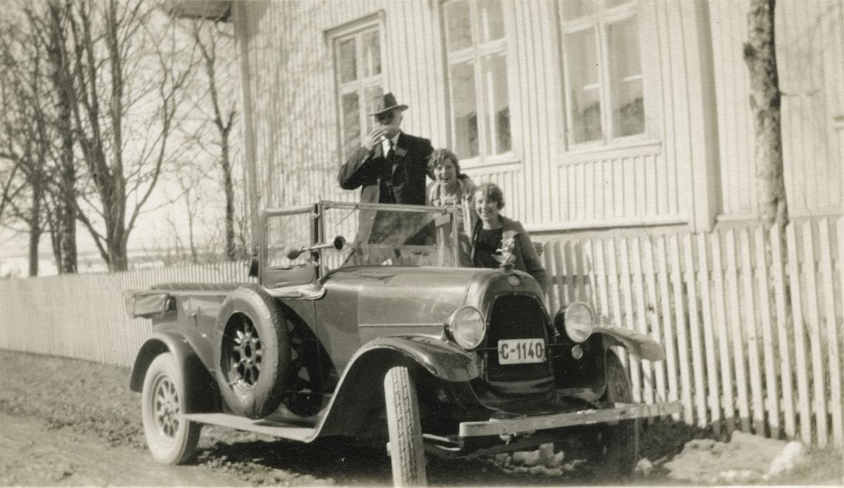 To damer og en mann ved bil (Citroën) foran hus.
