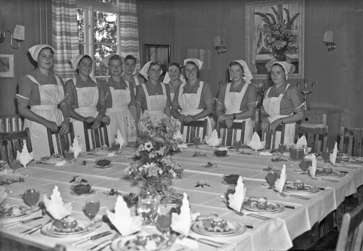 Jenter ved et dekket bord.