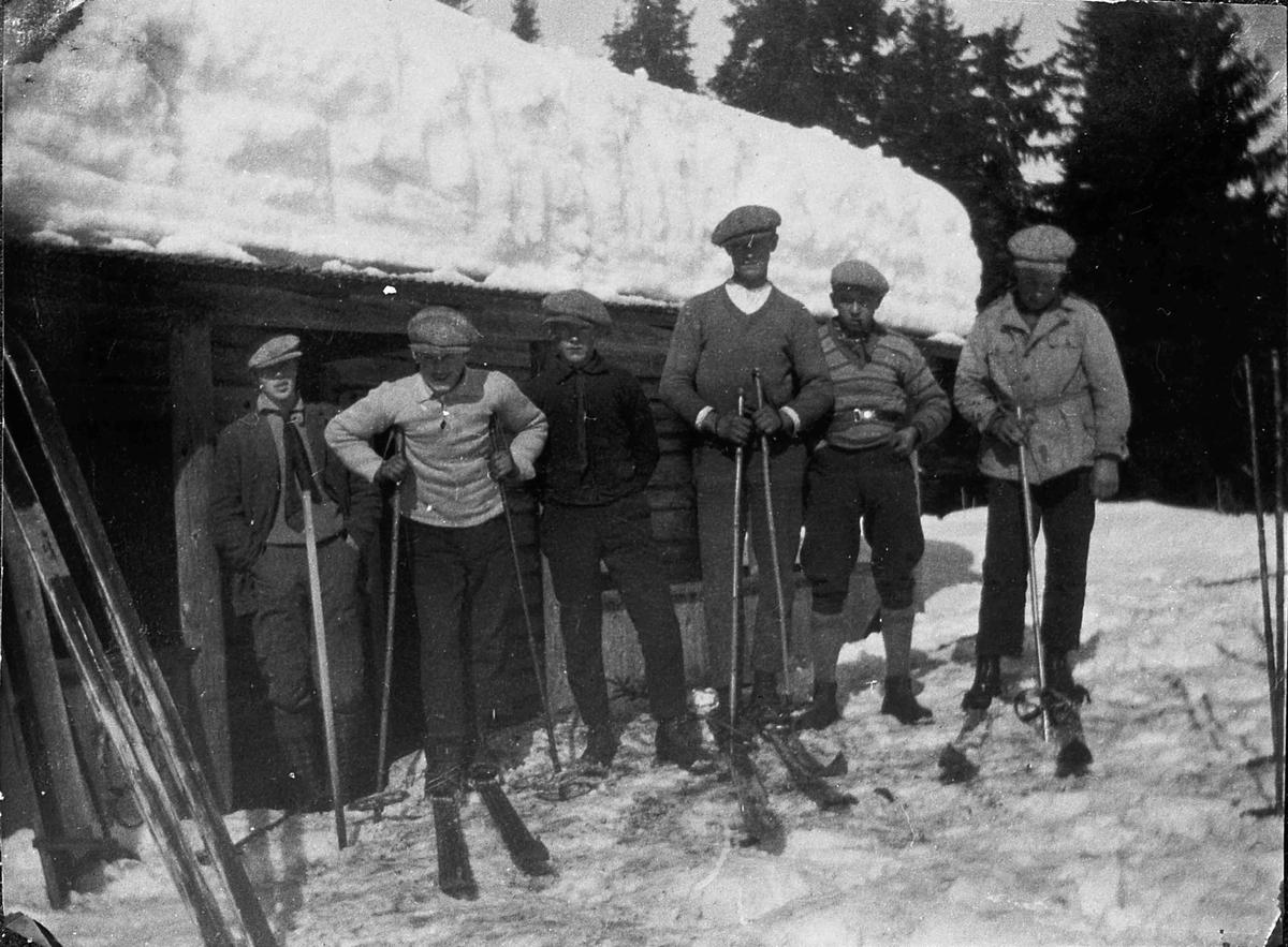 6 menn utenfor en hytte vinterstid.