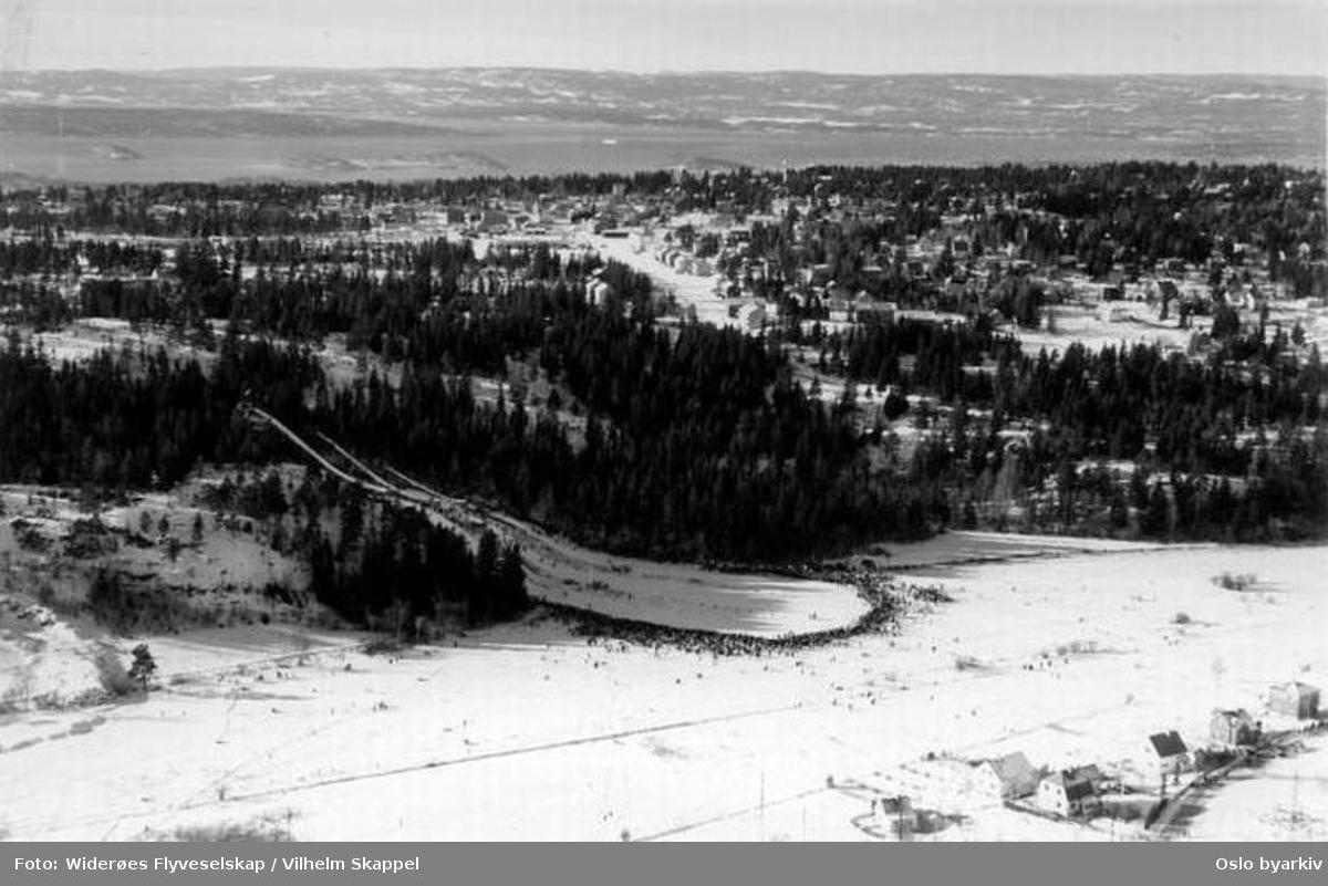 """Hoppbakke, skirenn - sannsynligvis fra de såkalte """"Guttenes Holmenkollrenn"""" med opptil 1000 deltakere. (Flyfoto)"""