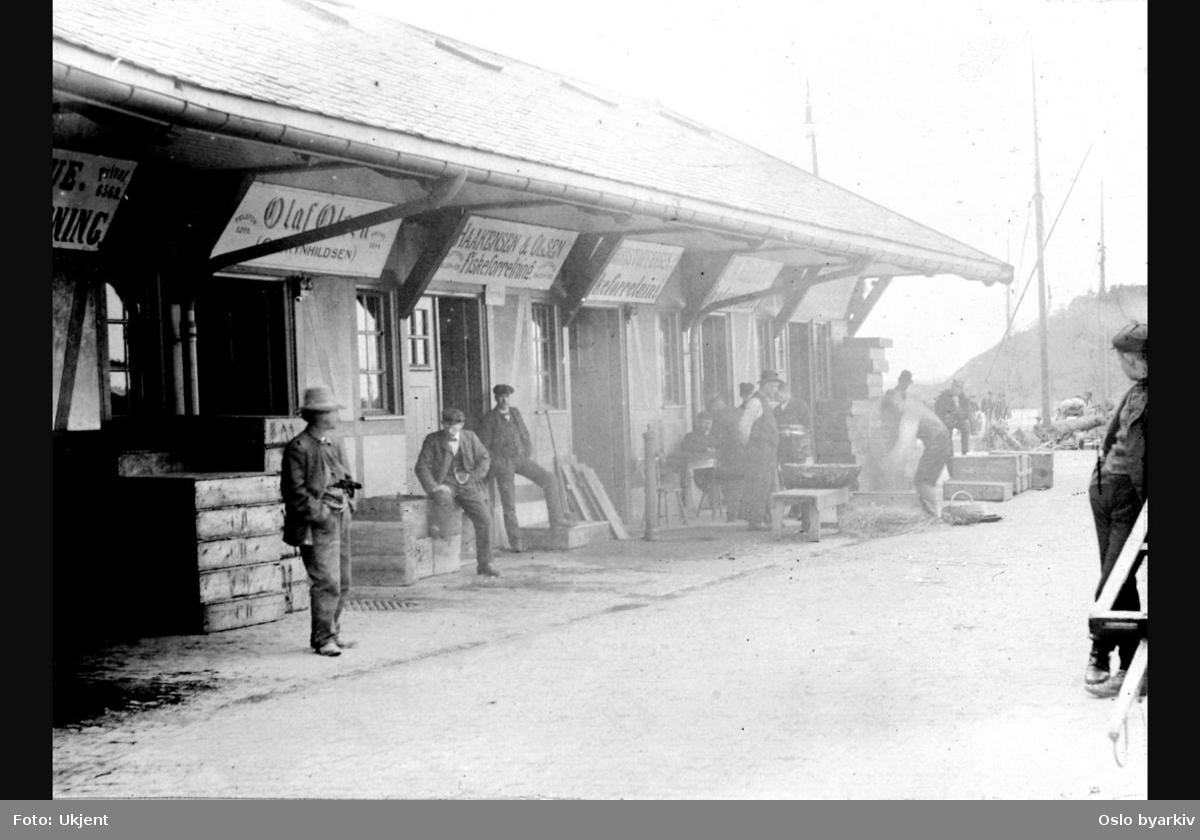Den nye fiskehallen fra 1905. Fiskeforretninger. Grossist-handlere venter på kunder. Tomkasser. Reklame / Skilt. Bildet er datert 23/5-06.