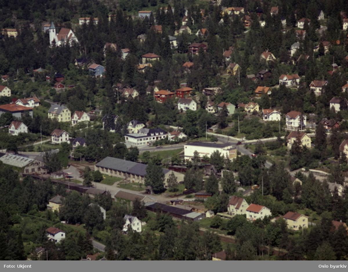 Holtet, Bekkelaget. Holtveien. Trikkestallene på Holtet og Jacobs bak til venstre. Hvit, firkantett bygg (daværende) Nordstrand kino. Foran til venstre Torsborgveien. Bekkelaget kirke i bakgrunnen. (Flyfoto)