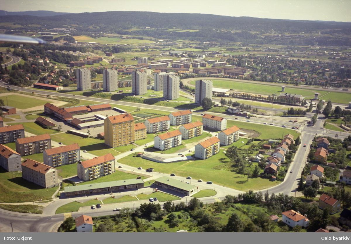 Årvollveien og Skolemesters vei i front. Trondheimsveien krysser Årvollveien til høyre. Årvoll skole bak gul høyblokk. Bjerke og Bjerke travbane i bakgrunnen.  (Flyfoto)
