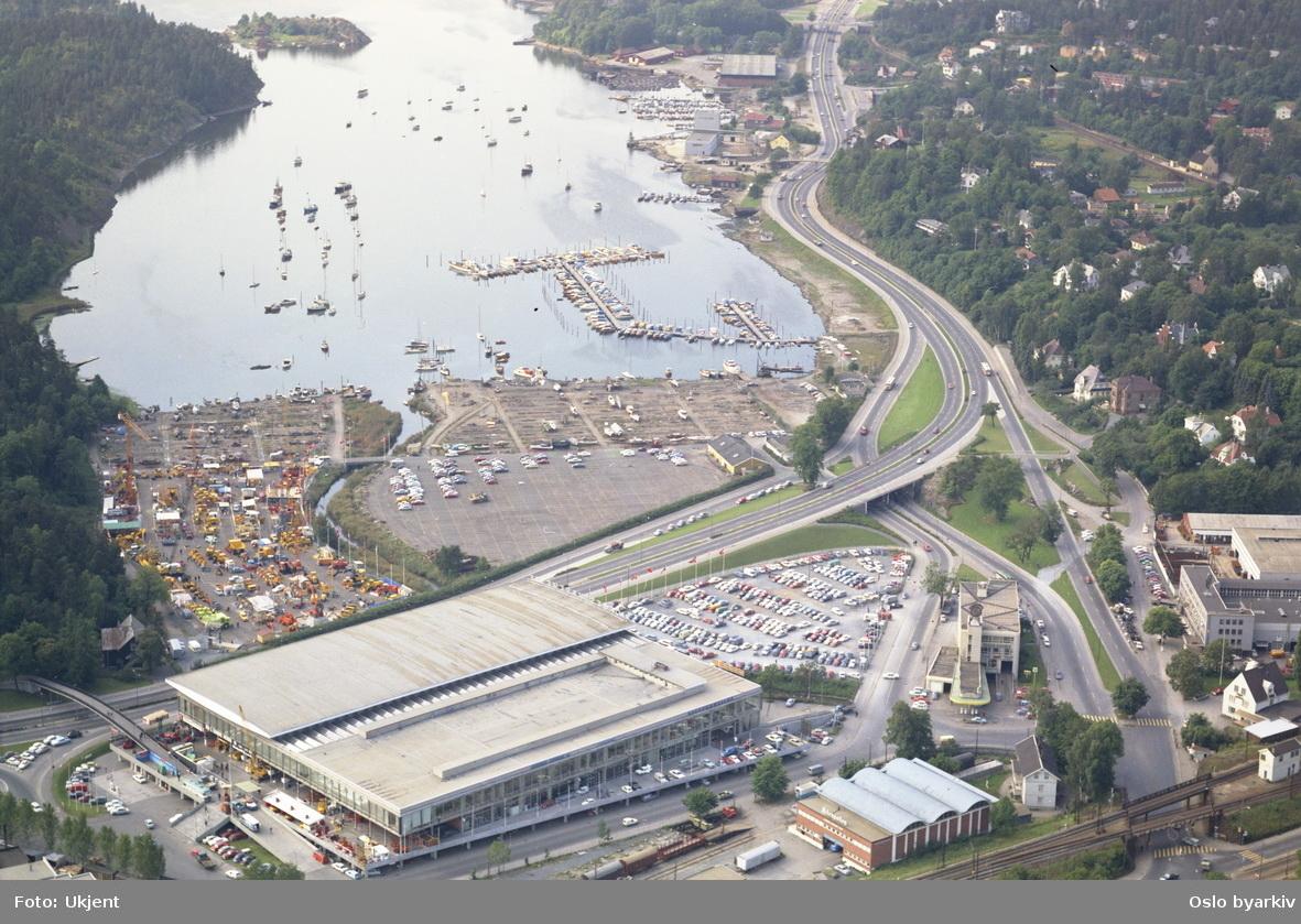 Norges Varemesse på Sjølyst. Sjølystveien passerer bak Messehallen. Jernbanesporet til Drammensbanen går i bru over Drammensveien nede til høyre. Bestum og Bestumkilen i bakgrunnen. (Flyfoto)