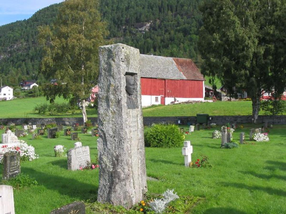 Ca 2 meter høg hoggen stein med broserlief. portrett av P. Faleide