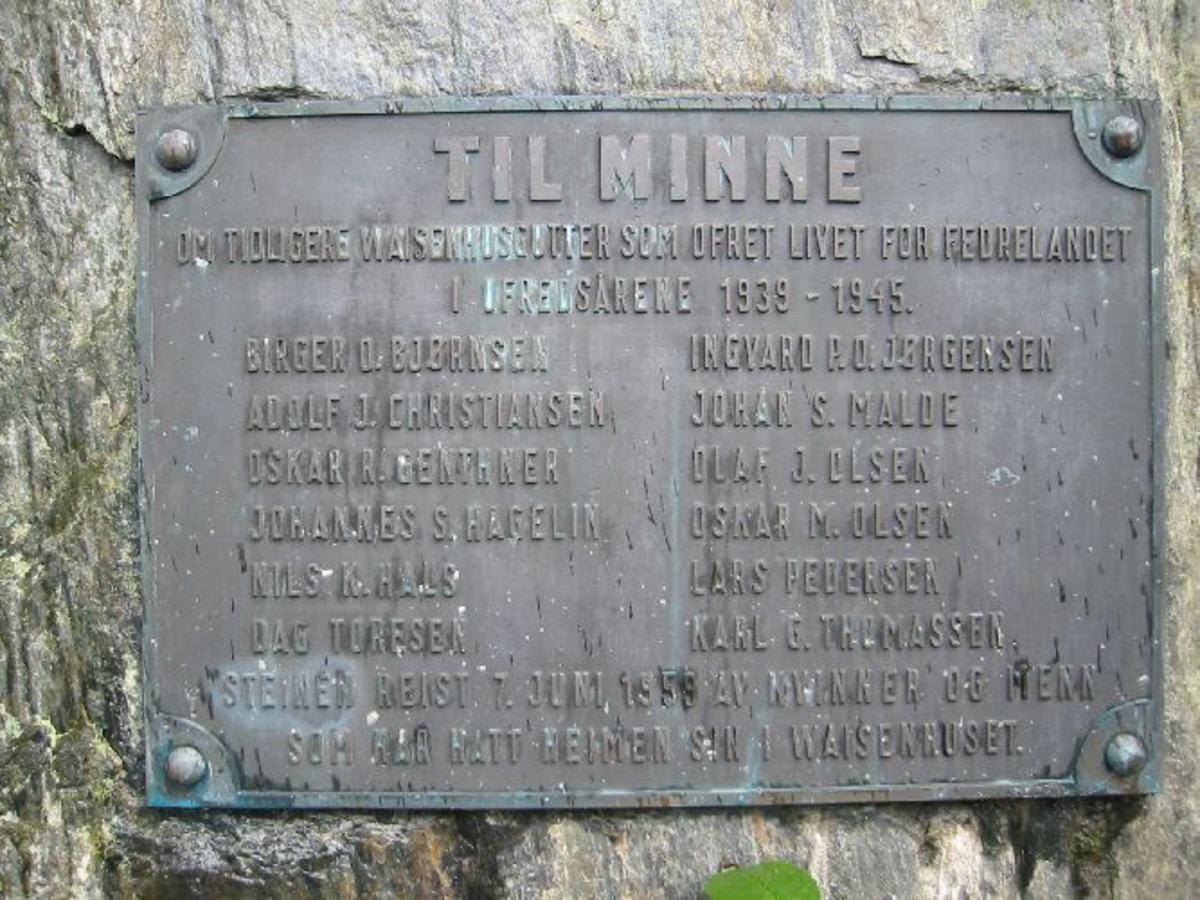 Bauta i gråstein med påsatt minnetavle i bronse . Steinen: H 1,75 m B 1,50 m D 0,40 m. Bronseplaten : B 0,62 m H 0,43 m. Utformet som en minnelund 4 m. X 3 m. Hellelagt med 2 søyler med kjetting mellom