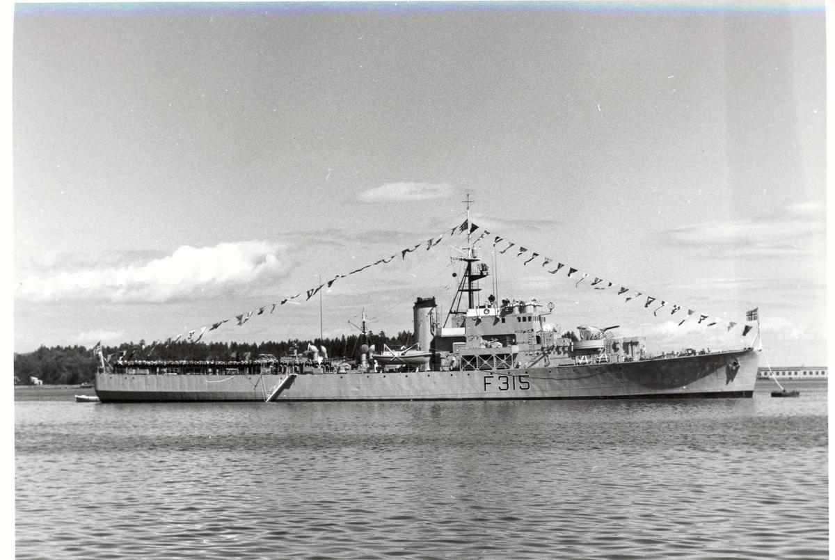 Motiv: River-kl. fregatt KNM GARM (F 315) Styrbord bredside. Stor flagging.