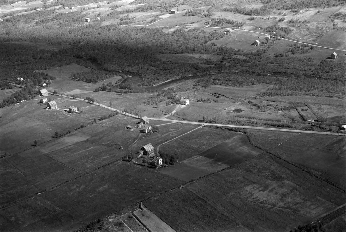 Flyfoto av ukjent sted med elv og gardsbruk.