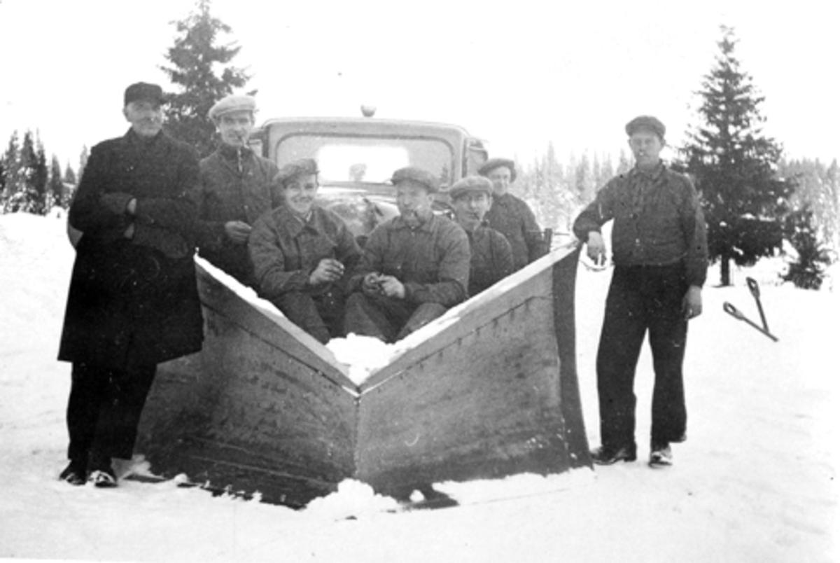 Lastebil med snøplog ved Elvstua i Furnes Almenning. Vinter. Fra venstre er Helmer Amdal, Asbjørn Rønningen, Asbjørn Havik, Alf Nordengen, Hjalmar Havik, Ludvig Ødegården, Einar Jevanord. Snøbrøyting, brøytebil.