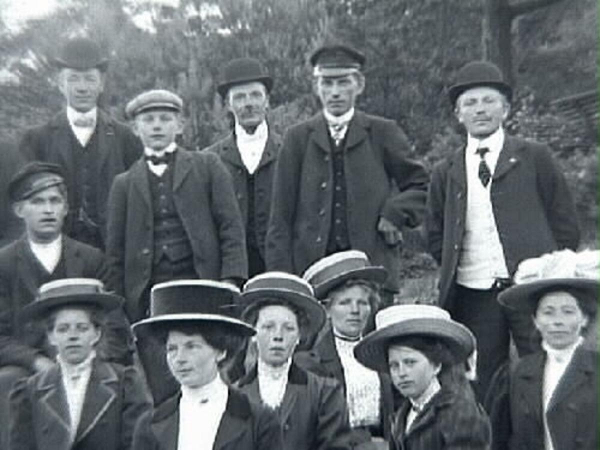 Gruppbild med c:a tjugo personer fotograferade utomhus. Mannen med plommonstop, stående trea fr vänster är Klas Johansson i Stenshult, född 1888.