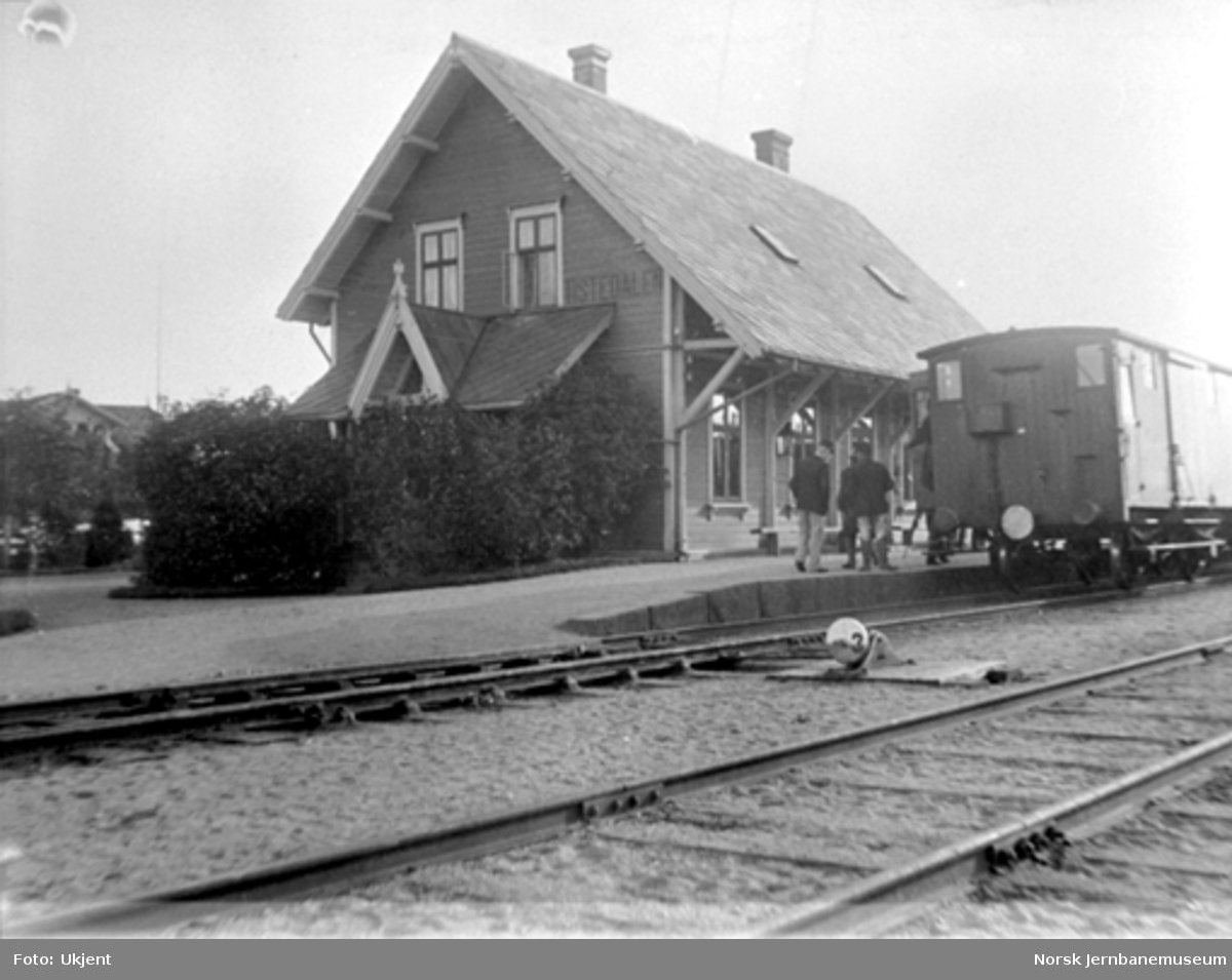 Tistedal stasjon med stasjonsbygningen og en F-vogn bakerst i et tog i spor 1