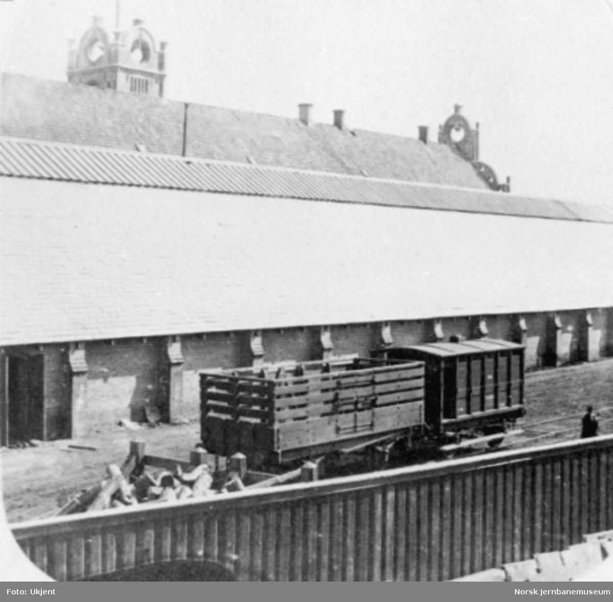 Godsvogn og bremsevogn med stasjonshallen i bakgrunnen - bremsevogn F nr. 4