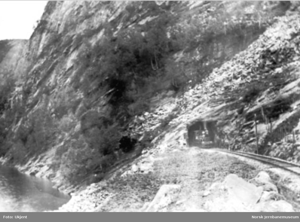 Damplokomotiv kommer ut vestre ende av Kløftefjell tunnel på Vossebanen, trolig under en befaring