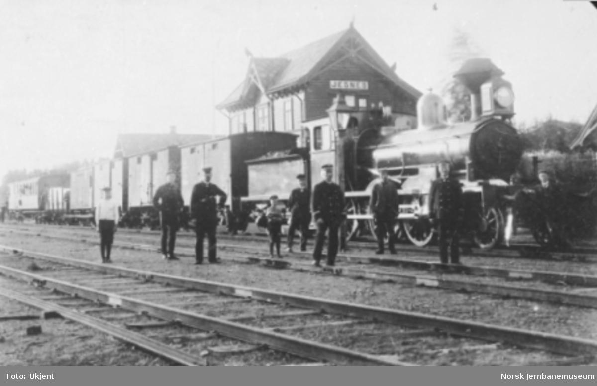 Damplokomotiv type 11b nr. 76 el. 77 foran blandet tog på Jessnes stasjon; stasjons- og togpersonalet er oppstilt foran toget