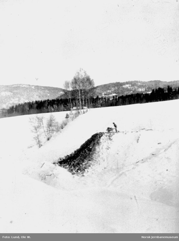 Fra anlegget av Holmestrand-Vittingfossbanen : en mann tipper trillebår ved Haslestad stasjon