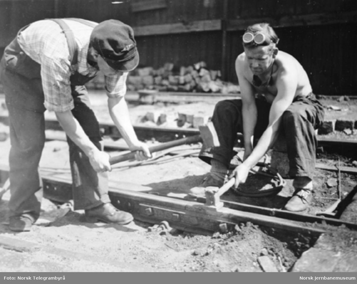 To mann i arbeid med en skinneskjøt i forbindelse med sveising