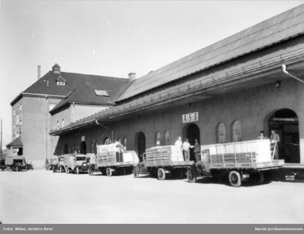 Tre lastebiler fra Statsbanenes automobilavdeling lastes opp utenfor godshuset på Østbanen