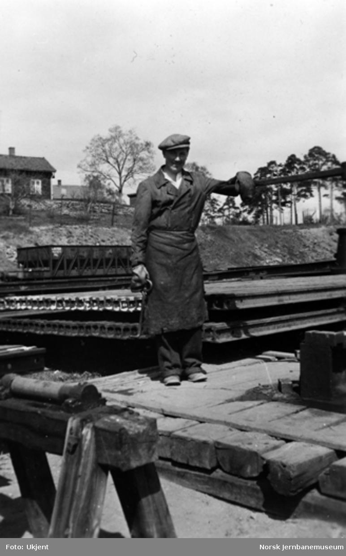 Mann på skinnelager - malmvogn fra Dunderlandsbanen i bakgrunnen