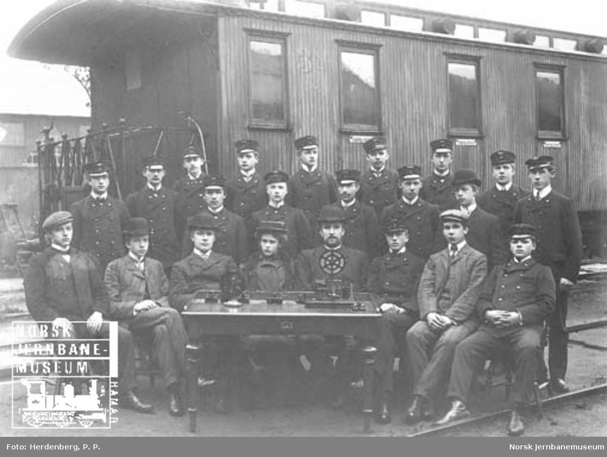 Gruppebilde med 22 telegrafistelever foran personvogn litra Co nr. 340 og bak et bord med telegrafiapparater