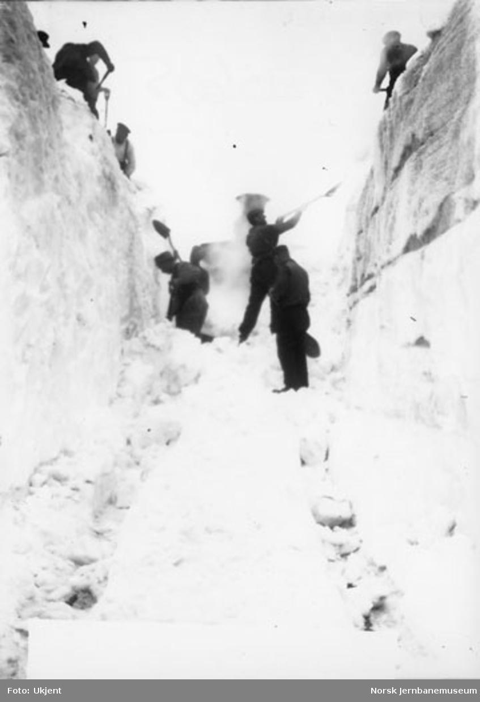En gjeng snømåkere ved inngangen til skjæring eller tunnel med et damplok i bakgrunnen