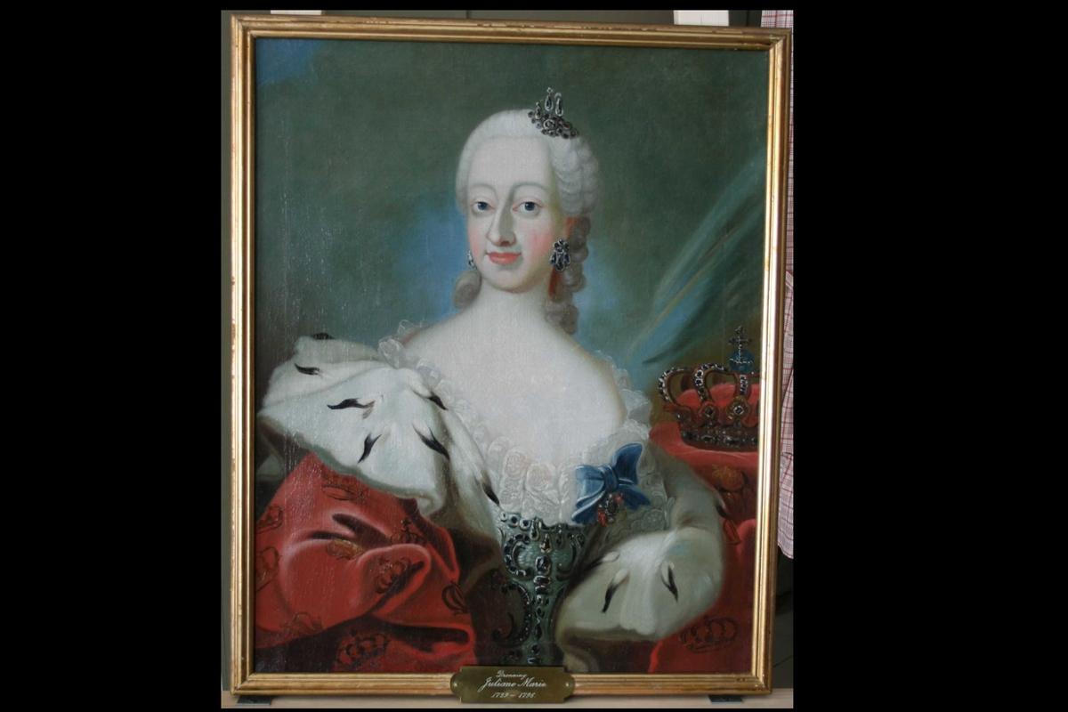Dronning Juliane Marie av Danmark-Norge. Kvinneportrett i halvfigur. Rokokkodrakt og kappe med hermelin. Parykk, juveler i parykken og på drakten. På bordet til venstre en kongekrone. Bakgrunn gråblå.  Orden festet til drakten.