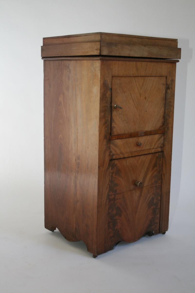 Toalettmøbel i mahogni. Toppplate til å åpne, skap og to skuffer. Nederste skuff har nattpotte eller bekken i blikk.