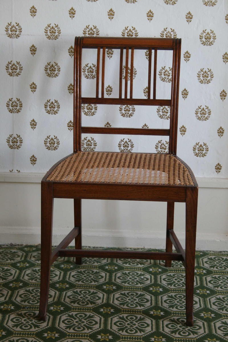 Spinkel stol i mahogni, med rottingsete, smale spiler i ryggen. 5 stoler og 1 kanapé.