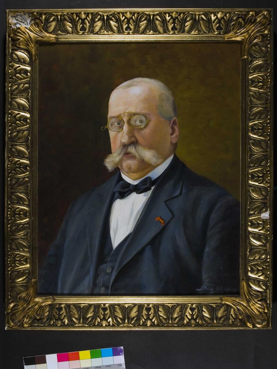 Portrett av Albert J Lange. Grått hår og bart, briller, mørk jakke og vest, hvit skjorte, sløyfe i halsen.