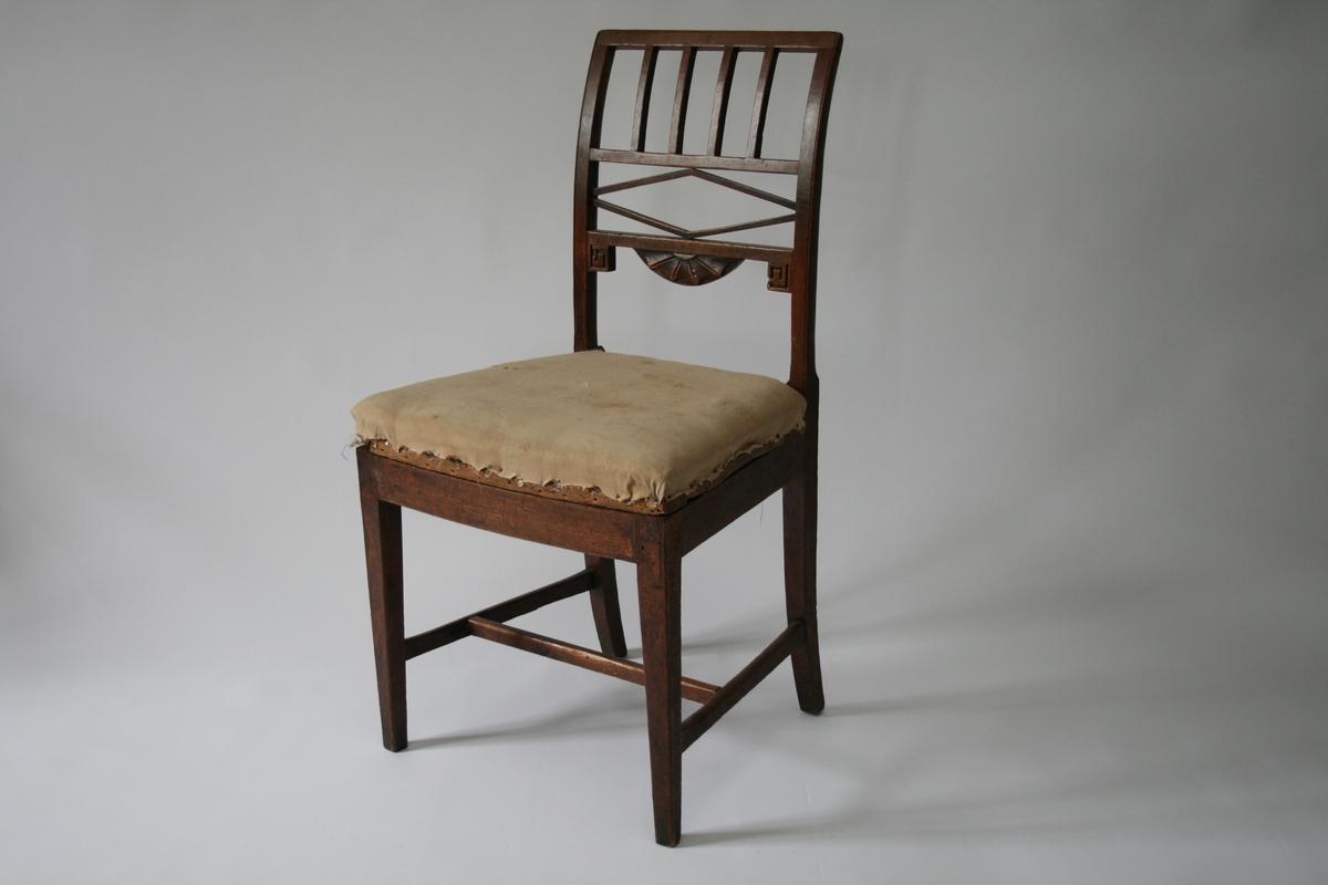 Én av to stoler i bøk, brunbeiset. H-sprosser, ryggspiler og skårne elementer i ryggparti. Løst sete med stopping og tekstil.