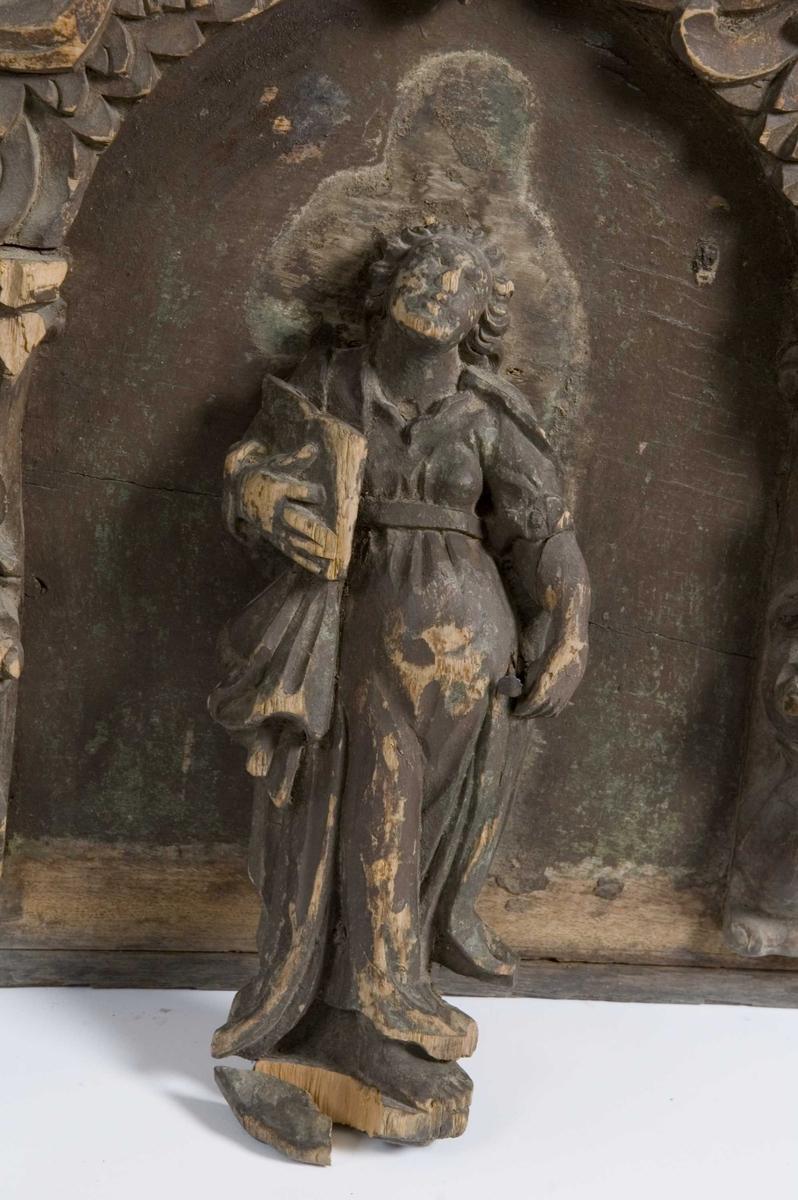 Kiste med flatt lokk. Utskårne figurer, engler og frukter i høyt relief.