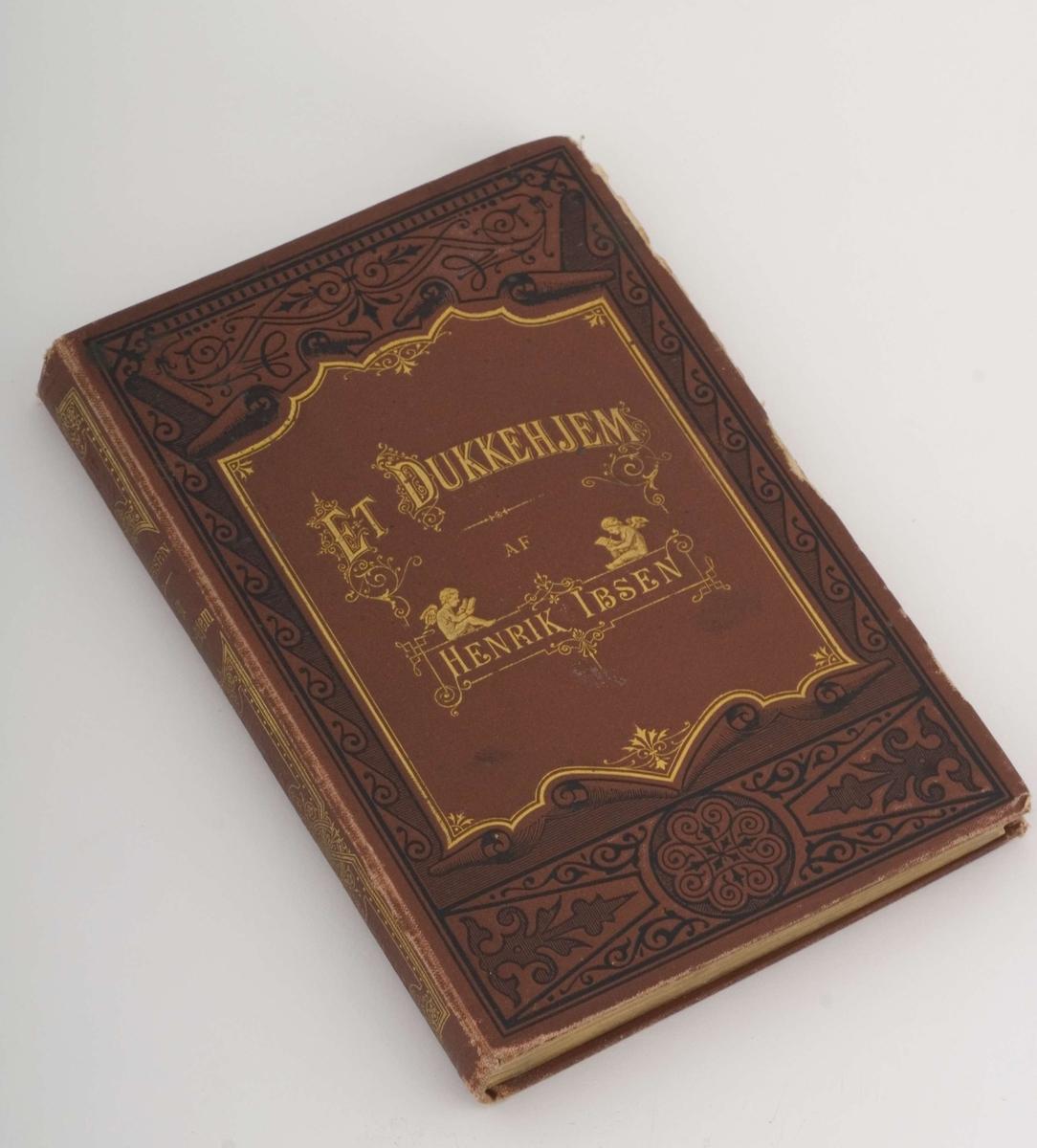Førsteutgave av Henrik Ibsen: Et dukkehjem med. Rødt omslag med preget mønster og gulldekor samt helt gullsnitt.