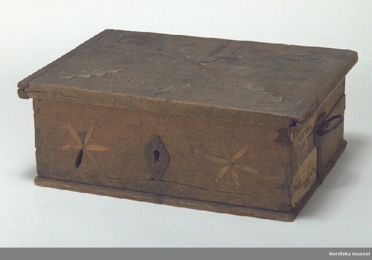 """Inventering Sesam 1997-1998: B 52,5, Djup 38,5, H 20 cm Matskrin, rektangulärt, med plant fällock, av lövträ, ek, utom botten som är av barrträ. Utanpåliggande botten, ihopsatt av två brädor, fästad underifrån med dymlingar av trä, fotlist. Sidorna ihopfogade genom sinkning. Locket med lister på kortsidorna, fästade med spikar. Två bandgångjärn, spetsformade, fästade på lockets insida samt på baksidan, målade i svart invändigt, cirkelornering. Bygelhandtag av järn, fästade i beslag på vardera gaveln, beslagen är fästade runt bottenkanten. Lås saknas, låssprint av järn finns kvar i locket, romboid nyckelskylt av järn. Locket och framsidan med inläggningar i lövträ, bladrosetter, hjärtan och """"granar"""", på locket """" AN 1761 """" i intarsia. Två papper med handskriven, otydlig text klistrade på insidan. En lapp på ena gaveln med bläckskrift """"Herr Doktor Arth. Hazelius  Etnografiska museet  Drottninggatan  Stockholm"""" samt två etiketter """"STOCKHOLM CENTRAL"""" samt """"Ilgods fr. Eksjö"""". En bit av intarsian saknas på framsidan. Sprickor i lock, botten och ett par av sidorna. Agnetha Blomberg 1997"""